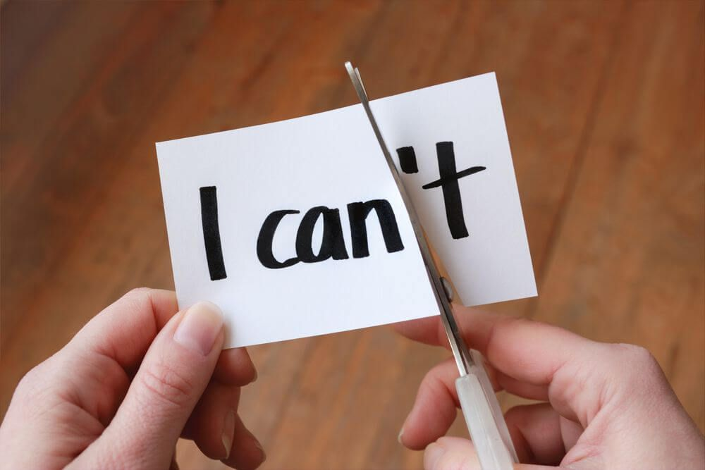 hands cutting paper text from I can't to I can