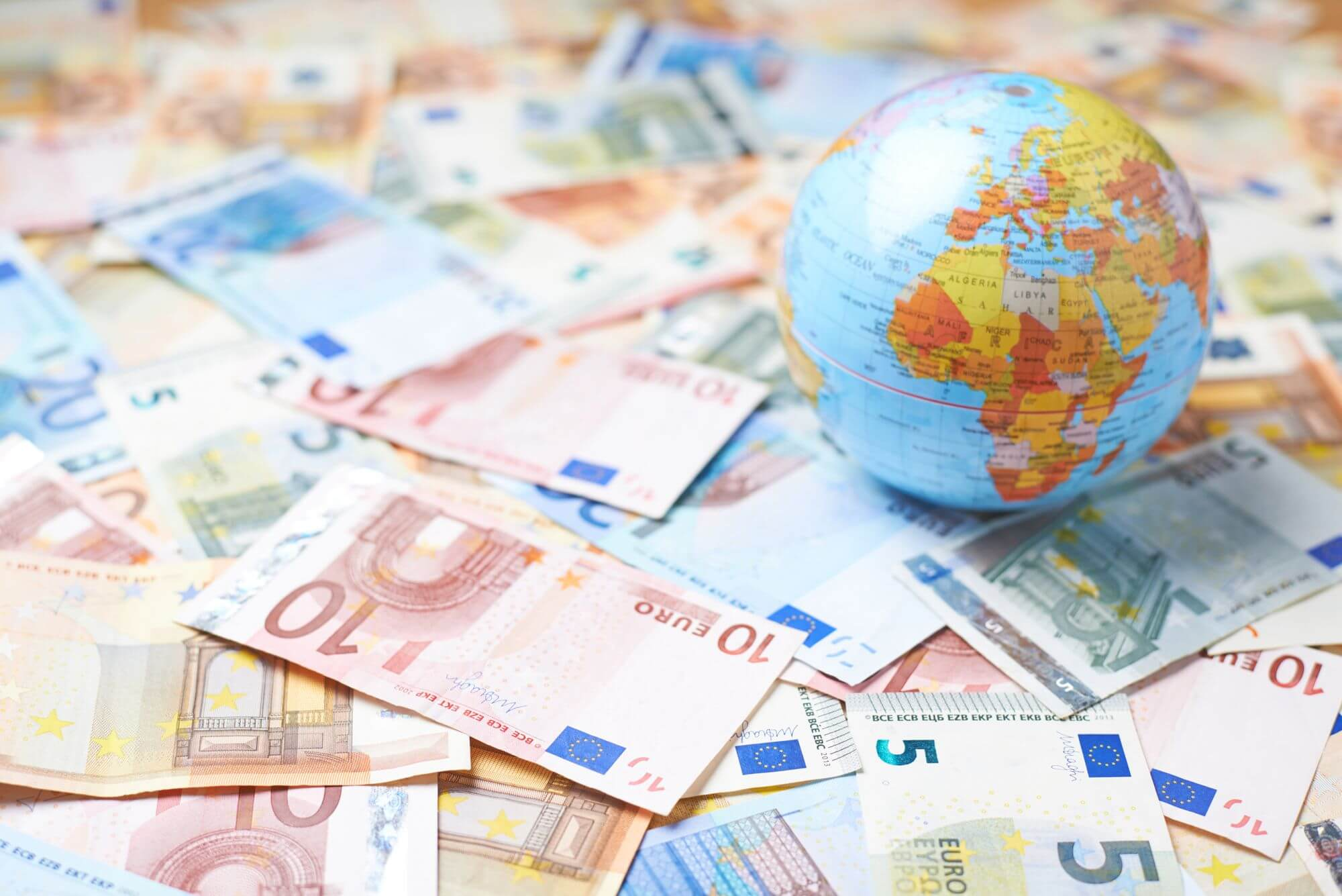 stack of foreign currency on globe