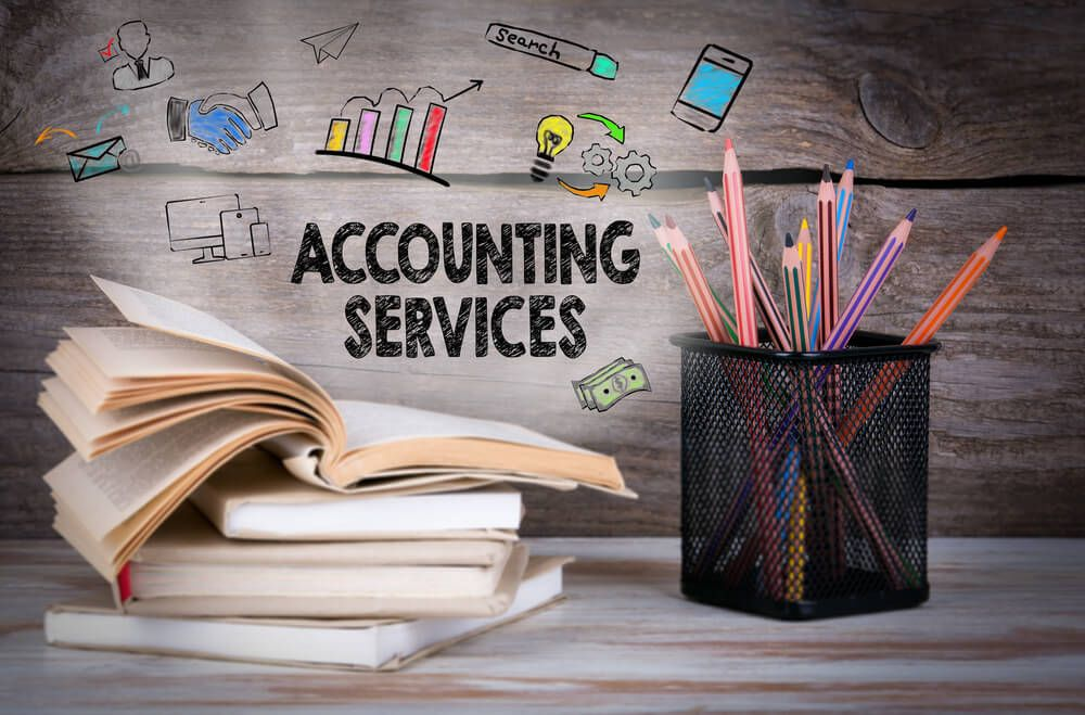 Accounting Services is written and Stack of books and pencils on the wooden table
