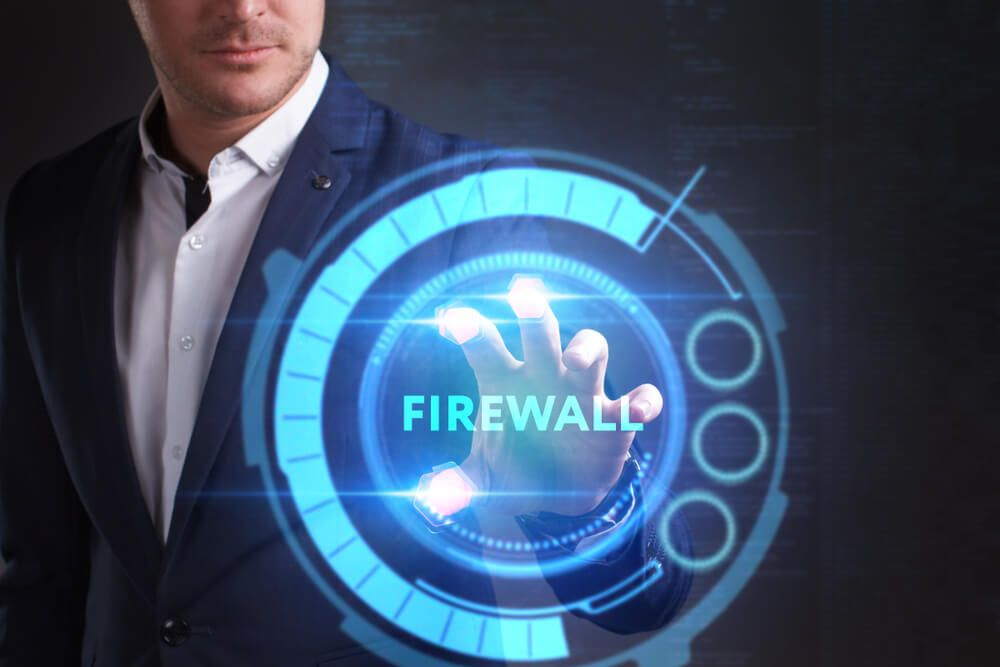 businessman working on a virtual screen of the future and sees the inscription Firewall
