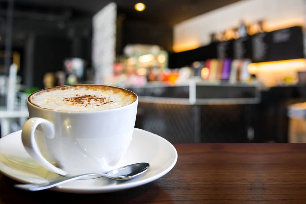 interior of a coffee shop and coffee cup focused