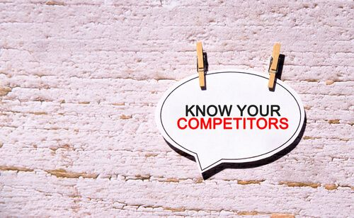 KNOW YOUR COMPETITORS on a white sheet with wooden pins