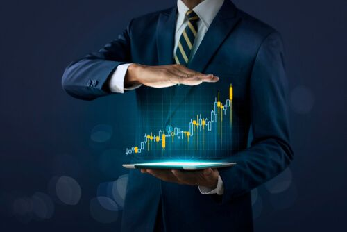 Businessman is showing a growing virtual hologram stock on dark tone background