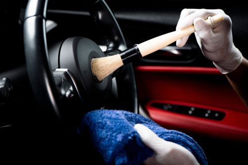 hands cleaning the steering wheel of the car