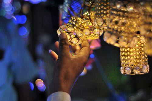 a man touches decorative items of diwali