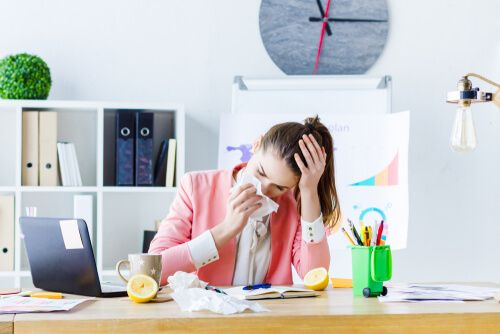 girl employee with flu, headache and runny nose working in office.