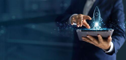 businessman holding tablet with a rocket hologram
