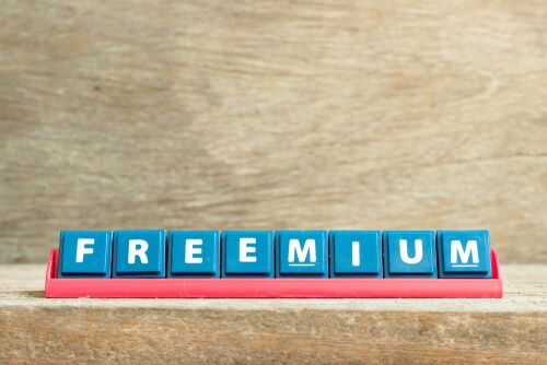 Tile letter on red rack in word freemium on wood background