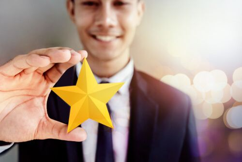 Businessman in black suit Smiling and Showing a Golden Star in Hand
