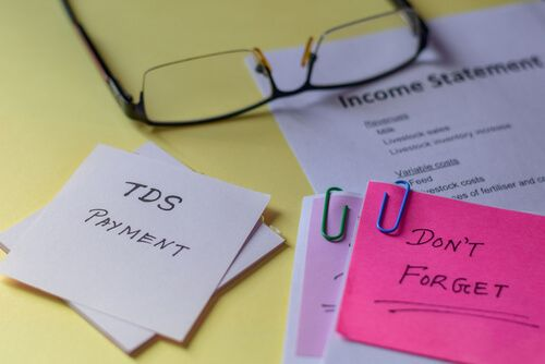 A note with text TDS payment laid on yellow background with other documents9