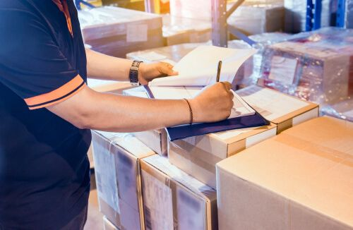 Warehouse worker is writing on clipboard with checking inventory of in warehouse