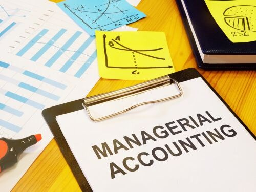 hand written text showing managerial accounting at white paper on cardboard