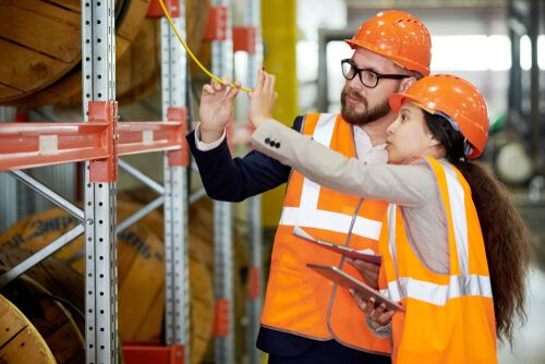 two modern factor workers wearing hardhats doing inventory in production warehouse