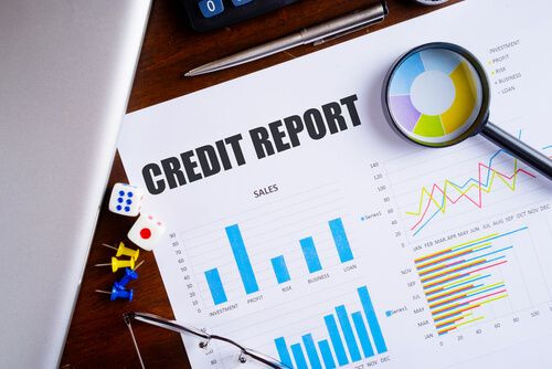 """""""Credit Report"""" text on paper sheet with magnifying glass on chart and dice on wooden table"""