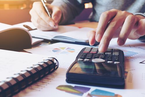 Hand man doing finances and calculate on desk about cost at home office
