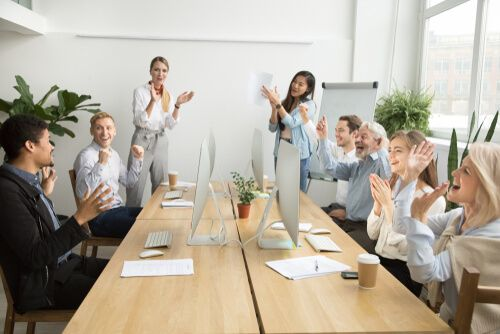team colleagues congratulating motivated coworker with success or achievement in office