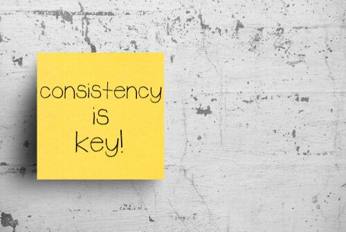 Consistency.is key word at Sticky note on concrete wall