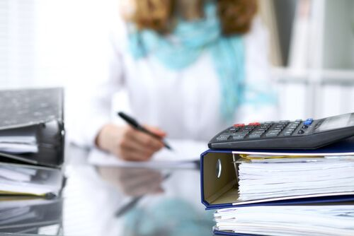 Calculator and binders with papers are waiting to processed by businesswoman back in blur.