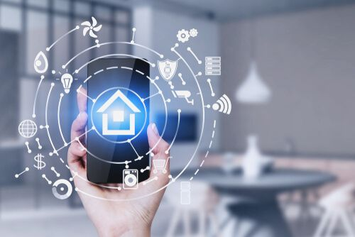 Hand of woman holding smartphone in kitchen with double exposure of smart home interface