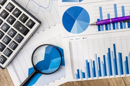 Business graph with magnifying glass and calculator pen on table