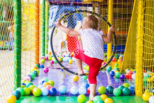 Little girl on the playground with coloured plastic balls