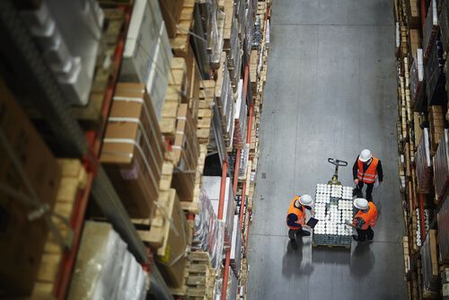 people working in large warehouse, counting goods on moving cart between shelves with packed boxes