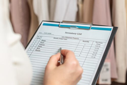 entrepreneur holding a clipboard with inventory list while doing inventory