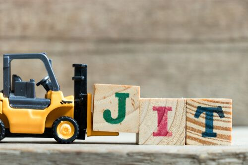 Toy yellow forklift hold letter block J to complete word JIT