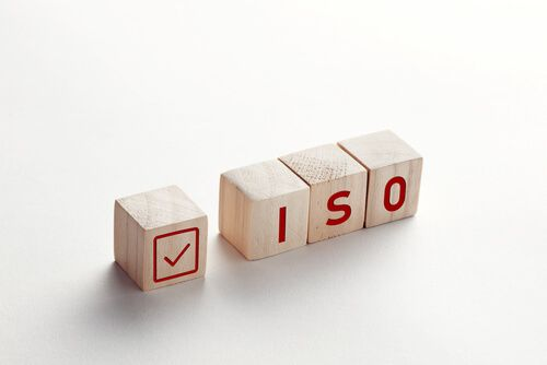 abbreviation ISO on wooden cubes with check mark on white background