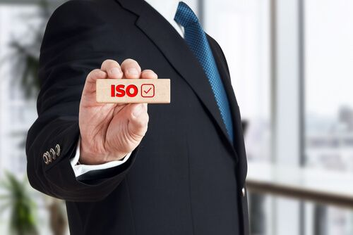 Businessman shows a wooden block with the word ISO with checkbox icon