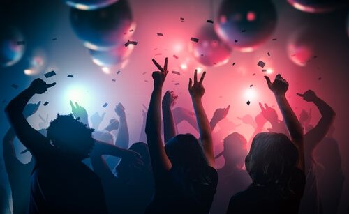 Young happy people are dancing in club