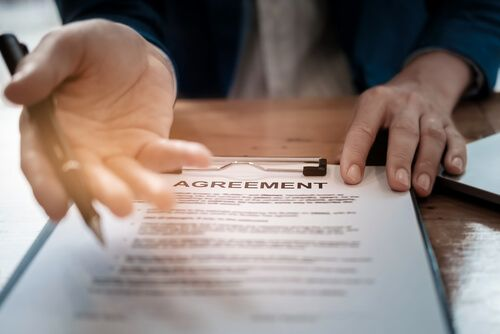 man gives pen and agreement to customer to sign