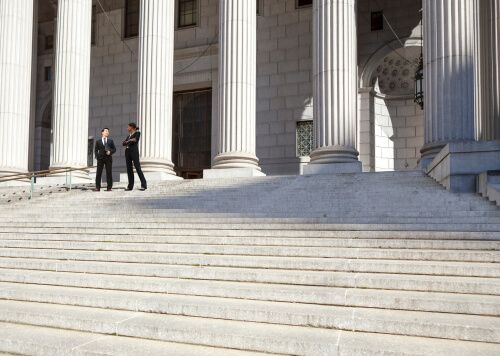 A well dressed man and woman converse on the steps of a legal
