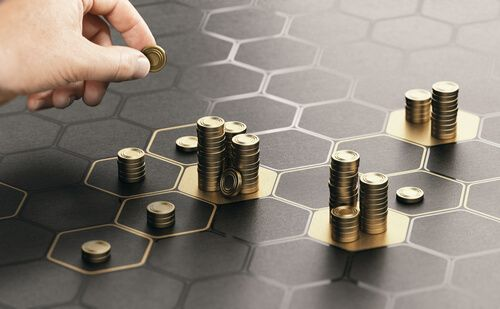 Human hand stacking coins over a black background with hexagonal golden shapes