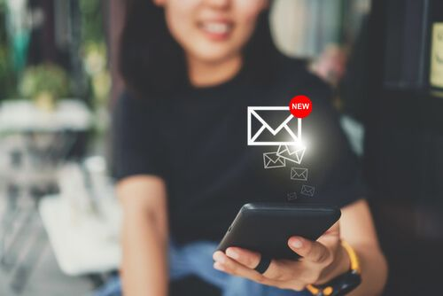 Woman hand use smartphone in public area with 1 new email alert sign icon pop up