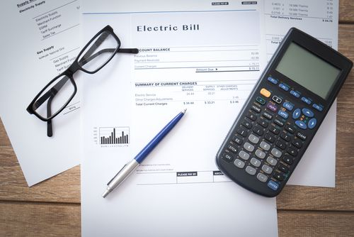 Electricity bill paper form on the table with pen, glasses and calculator