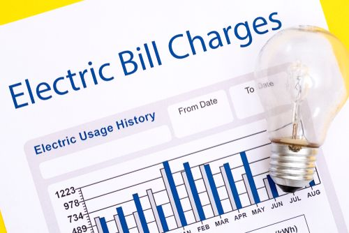Energy bill paper forms on the table closeup with a light bulb