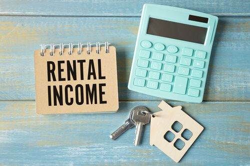 The word rental income is written in a notebook that sits on a grey desktop along with a laptop