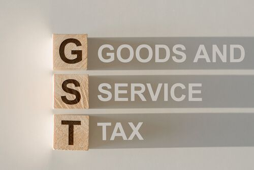 GST acronym for Goods and Services Tax in wooden alphabet letters with text on shadows
