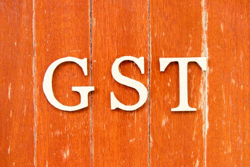 GST (Goods and Service Tax) on old red color wood plate background