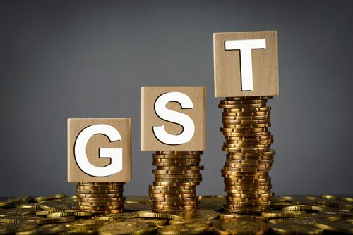 Wooden block with a GST word on stacked coins