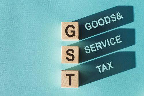 Wooden cubes building word GST on light blue background
