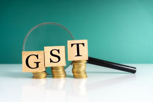 GST wooden cube on stacking coins with magnifying glass