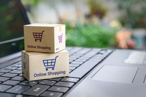 Paper cartons with a shopping cart or trolley logo on a laptop keyboard