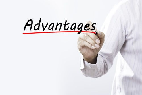 Businessman hand writing advantages with red marker on transparent wipe board