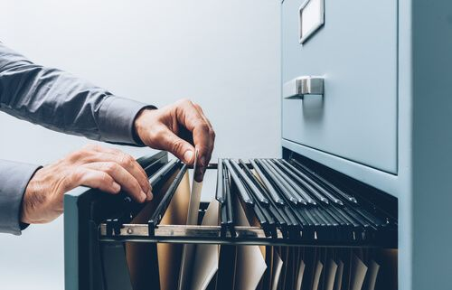 clerk searching for files into a filing cabinet drawer